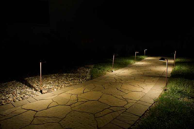 LED path lights - offset round copper path lights on sidewalk