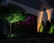 10 Watt LED Landscape Flood Light w/ Mounting Spike: Shown Illuminating Shrubs And Building Wall.