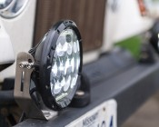 "7"" Round LED Sealed Beam Headlight - H6024 LED Driving Light: Showing Light Mounted On Jeep Bumper Using Included Mounting Bracket."