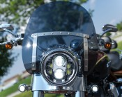 """7"""" Round Motorcycle Headlight - DOT Approved LED Headlight Conversion: Shown Installed On Harley In Chrome Finish With Daytime Running Lights On."""