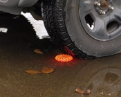 Rechargeable LED Road Flares being run over in a puddle to demonstrate water resistance and durability