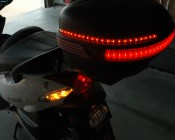Customer's Scooter with LED strips added to the cargo box for additional visibility.  He has three strips in the center lens for tail and brake lights with another strip on each side for turn signals.  Looks great! Thanks, Guy!