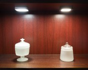 SSM-x3x - Surface Mount Square LED Puck Light Fixture installed in shelf.  Cool White (left) and Natural White (right