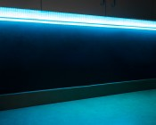 Corner Accent Aluminum Profile Housing for LED Strip Lights: Shown Installed Under Cabinet With Blue LED Strip And Etched Lens Option (Strip Sold Separately).