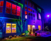 50 Watt RGBW LED Flood Light Fixture - Wi-Fi Compatible: Shown Illuminating Back Of House In Purple.