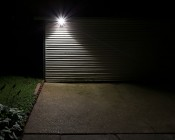 LED Motion Sensor Light - Single Head Security Light - 10W: Showing Beam Pattern Installed On Side Of Garage.
