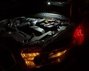 NEBO TWIN PUCKS LED Task Light and LED Safety Flare Combo: Shown Illuminating Under Car Hood With Safety Flare Attached To Side Of Car.
