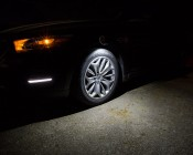 NEBO TWIN PUCKS LED Task Light and LED Safety Flare Combo: Showing Light's Beam Pattern On Car's Wheel.