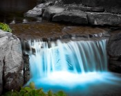 LED Underwater Pool Lights and Pond Lights - Triple Lens - 180W: Shown Illuminating Pond Waterfall In Blue.
